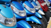 A row of mopeds or scooters for rental