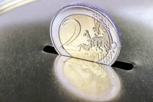 Two-euro coin inserting it into a piggy bank as savings