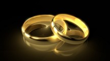 Two golden wedding rings isolated on black background.